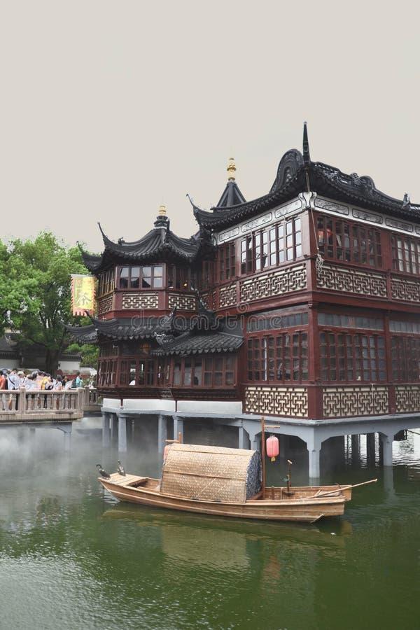 Reproduction du bâtiment de chinois traditionnel sur des échasses dans le lac avec le bateau de sampan photo libre de droits