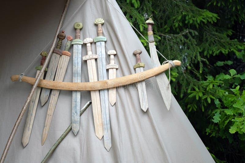 Reproductions médiévales en bois d'armes pour le combat rapproché montré sur la texture grise de tissu photos stock