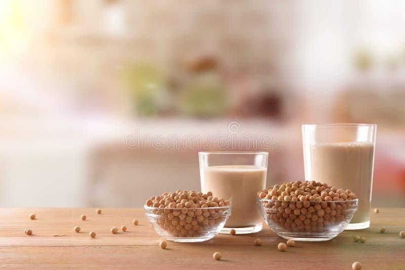Reptientes con leche de soja y los granos en cocina rústica afrontan foto de archivo libre de regalías