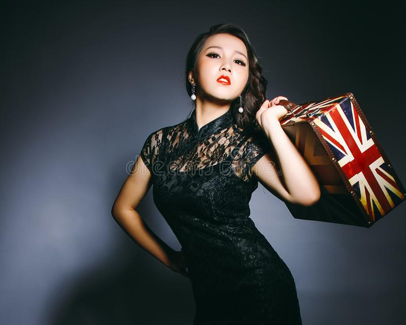 During the republic of China era, Asian women wore cheongsam and carried suitcases. royalty free stock images