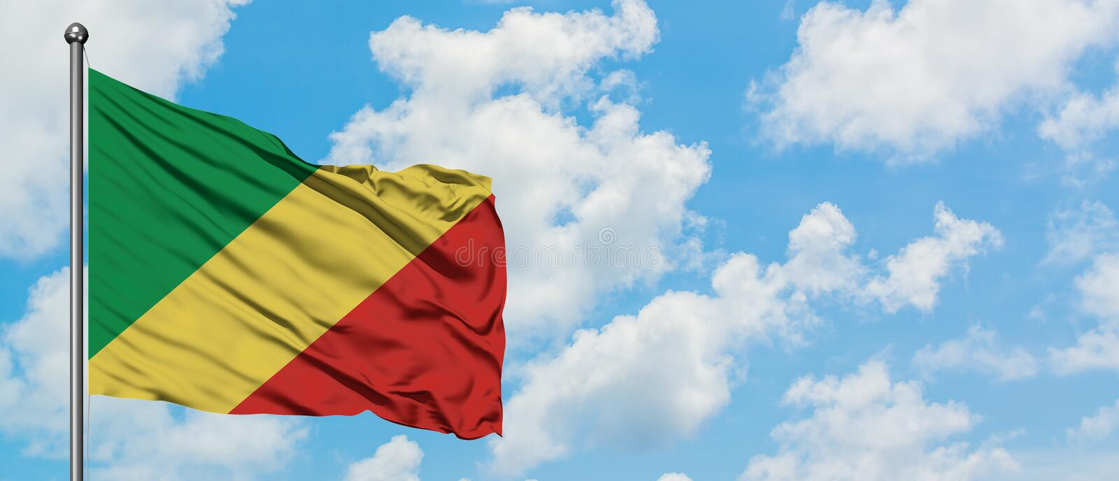 Republic Of The Congo flag waving in the wind against white cloudy blue sky. Diplomacy concept, international relations.  royalty free stock photo