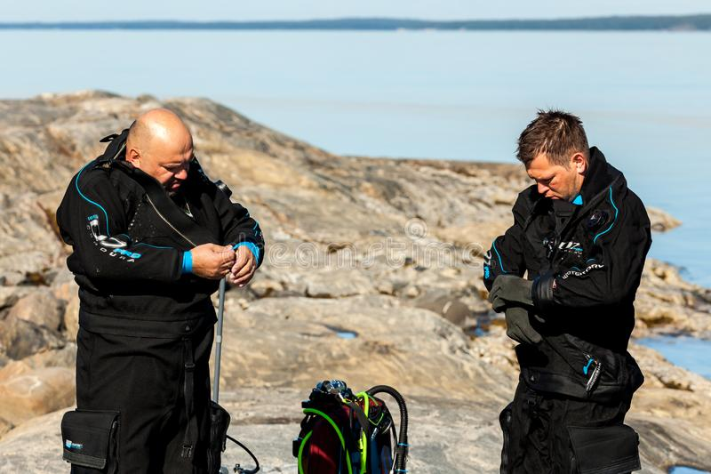 Republic of Karelia, Russia - August 19, 2015: Scuba divers checking their equipment and prepare to dive stock photography