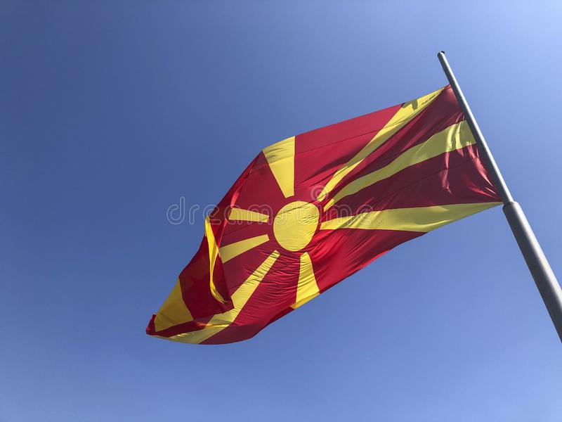Republic of North Macedonia flag waving on sky royalty free stock photography