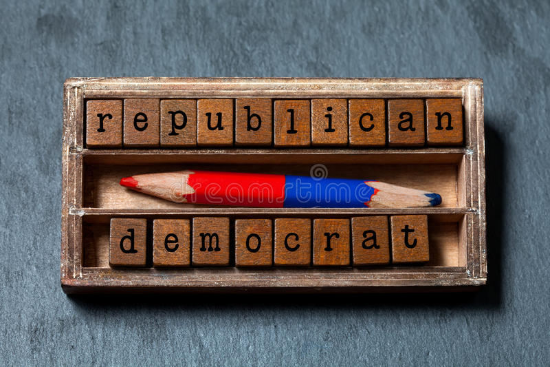 Republican democrat politic alternative choice concept. Vintage box, wooden cubes phrase with old style letters, red. Blue colored pencil. Gray stone textured stock image