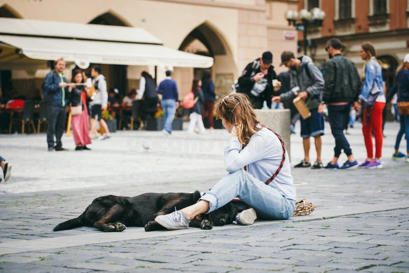Republika Czech, Praga, Lipiec 25, 2017: Piękny młoda kobieta malarz siedzi na podłoga po środku kwadrata i remisy, byli zdjęcia stock