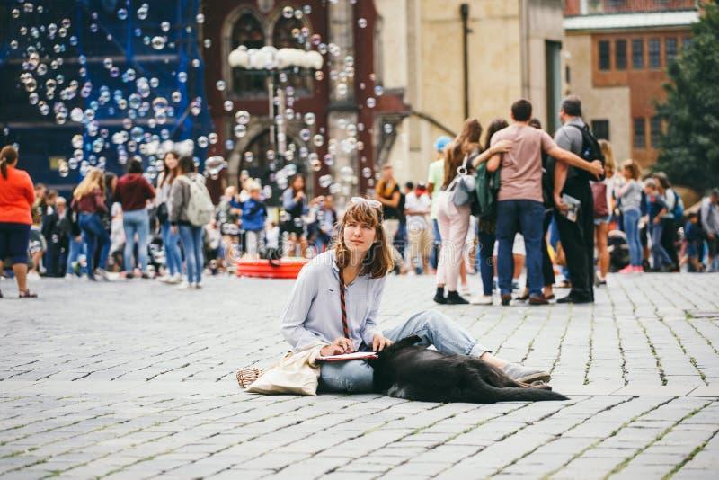Republika Czech, Praga, Lipiec 25, 2017: Piękny młoda kobieta malarz siedzi na podłoga po środku kwadrata i remisy, byli zdjęcie royalty free