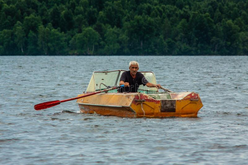 REPUBLIKA KARELIA ROSJA, LIPIEC, - 2, 2013: Stary z włosami garbnikujący mężczyzny żeglowanie na łodzi z paddles na karelian jezi zdjęcia stock