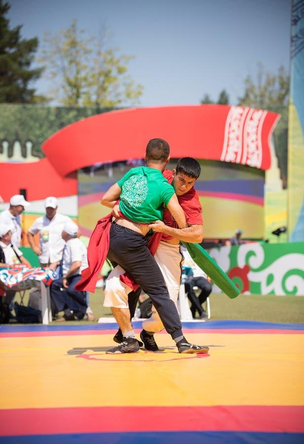REPUBLIKA TATARSTAN, ROSJA: 04 07 2019 - Dwa dysponowanego mężczyzny w zieleni i czerwieni walczą na ringowym Sabantui pojęciu zdjęcie stock