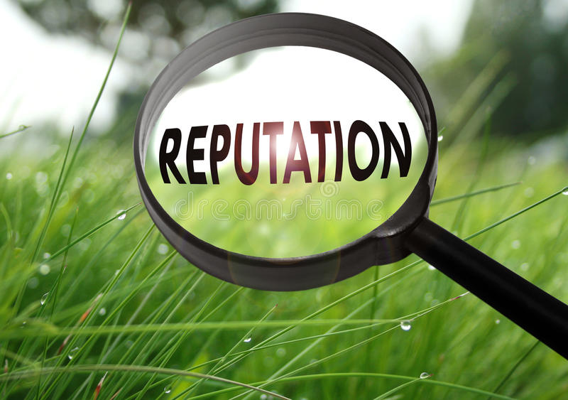 Reputation. Magnifying glass with the word reputation on grass background. Selective focus stock photography