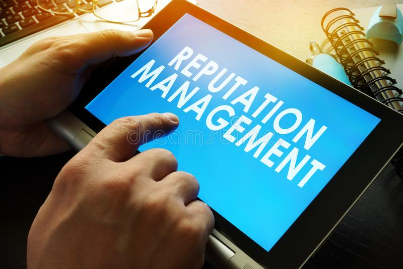Reputation management on a screen of tablet. Reputation management written on a screen of tablet royalty free stock images