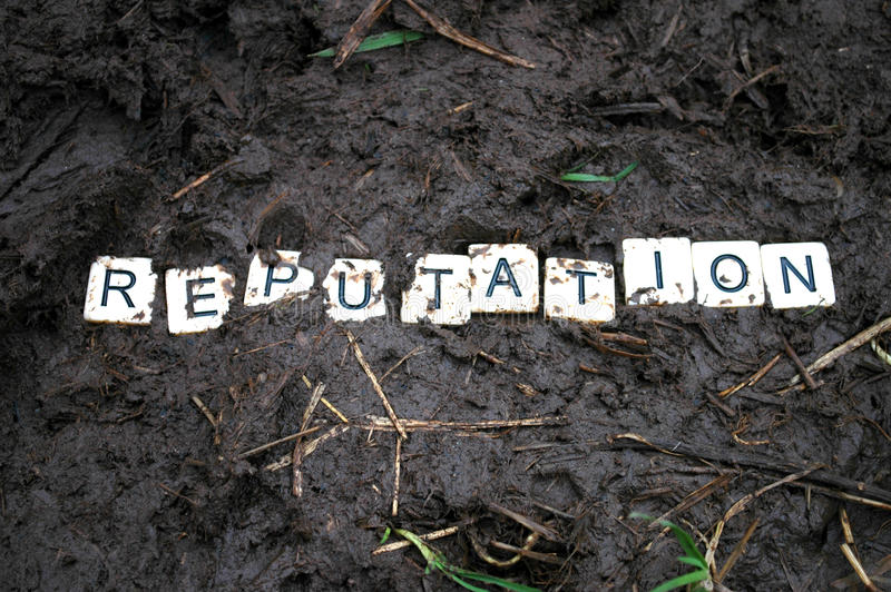 Reputation trampled in the mud. Letters spelling `reputation` being trampled in the mud stock photo