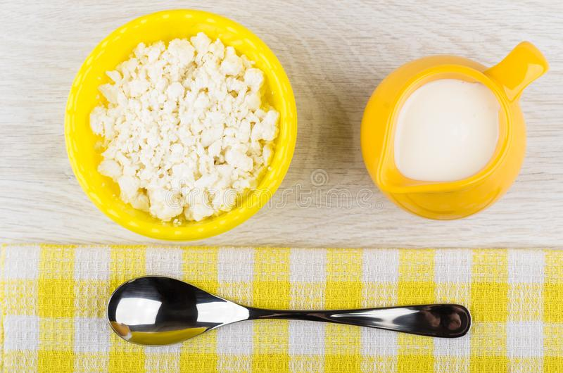 Requesón sin grasa en el cuenco, jarro con el yogur, cuchara, servilleta imagen de archivo libre de regalías