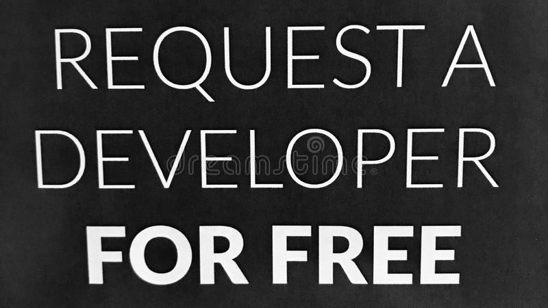 REQUEST A DEVELOPER FOR FREE SIGN in black. A sign at a freelance tech hub advertises that you can request a develop for no price royalty free stock images