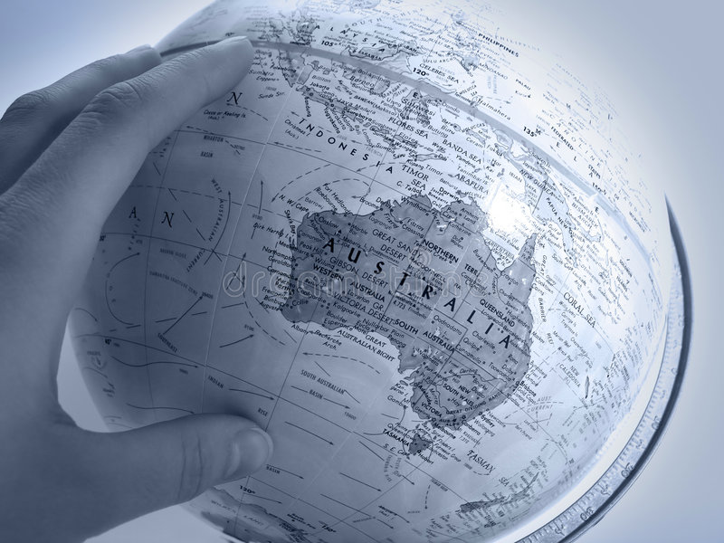 Request - Earth Study: Oceania. Handing about to turn the globe on its axis, focus on Oceania royalty free stock photography