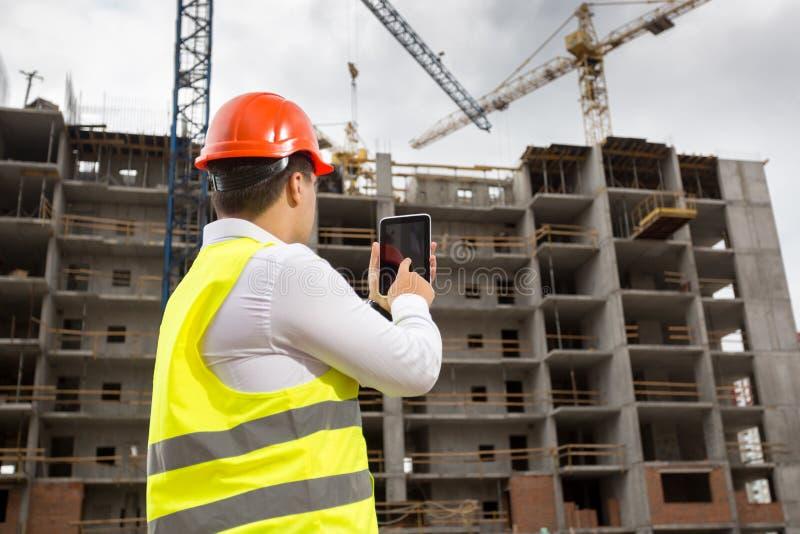Rera siktsfoto av affärsmannen, i säkerhetsväst- och hardhatanseende på byggnadsplats och att använda den digitala minnestavlan royaltyfria foton