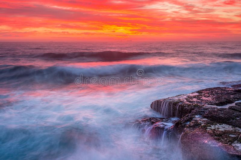 Res skies over ocean as waves surge over rocks. Reds and oranges paint the sky as waves surge over rocks in a never ending rhythm stock photo