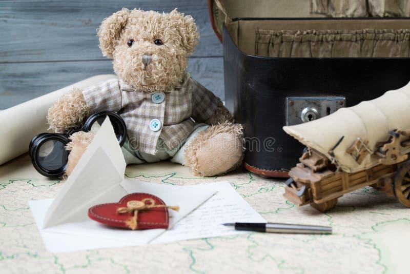 Resa begreppet, nallebjörnen med gammal kikare och resväskan på den antika översikten med bokstaven och en reservoarpenna arkivfoton