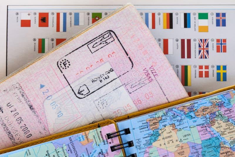 Resa begreppsbakgrund med översikten, passet med stämplar för det eget tillträdeet och färgrika nationsflaggor royaltyfria bilder