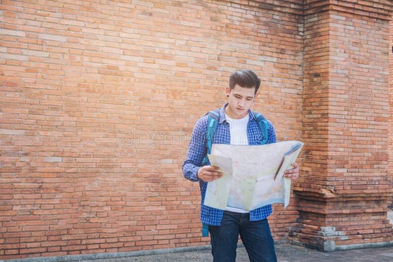 Resa den moderiktiga blicken för mannen som söker riktning på lägeöversikt medan arkivbilder