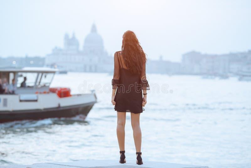 Resa den turist- kvinnan på pir mot härlig sikt på den venetian chanalen i Venedig, Italien arkivfoton