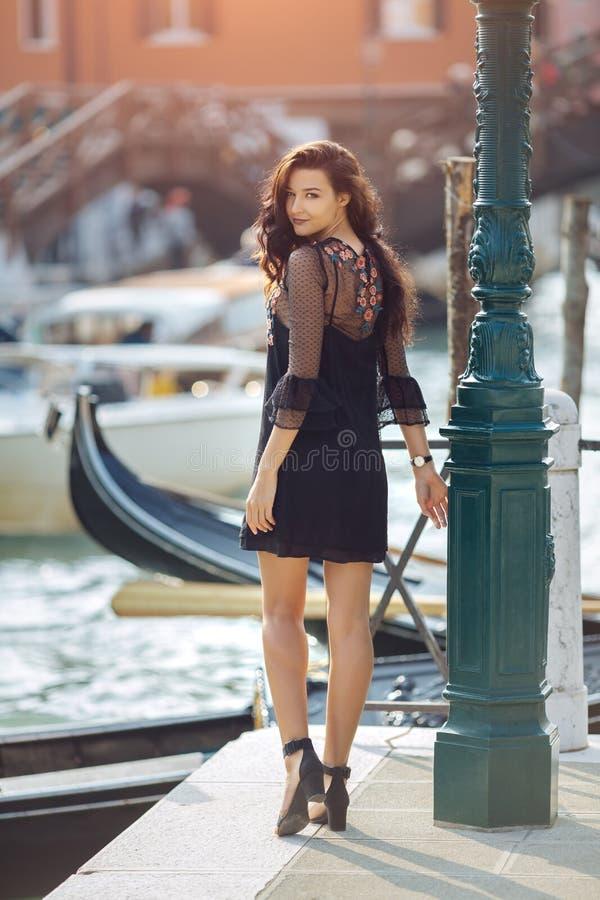 Resa den turist- kvinnan på pir mot härlig sikt på den venetian chanalen i Venedig, Italien royaltyfri bild