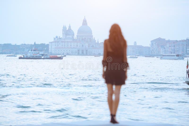 Resa den turist- kvinnan p? pir mot h?rlig sikt p? den venetian chanalen i Venedig, Italien arkivbild