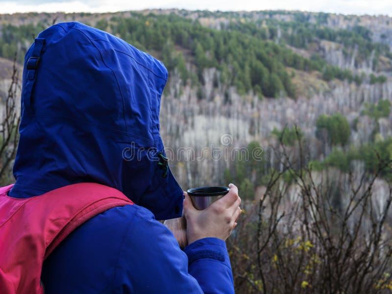 Resa flickan som dricker från en råna på skog- och bergbakgrund Flicka på semester som tycker om skönheten av naturen royaltyfri bild