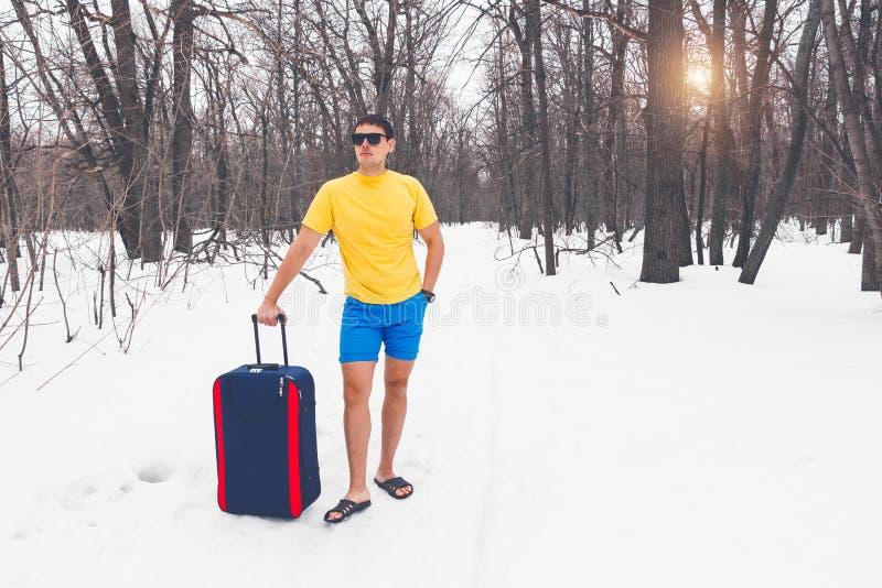 Resa från vinter till sommar Den unga mannen står i sommarclothers på snön och drömmarna av semestern, havet, varmt exotiskt land fotografering för bildbyråer