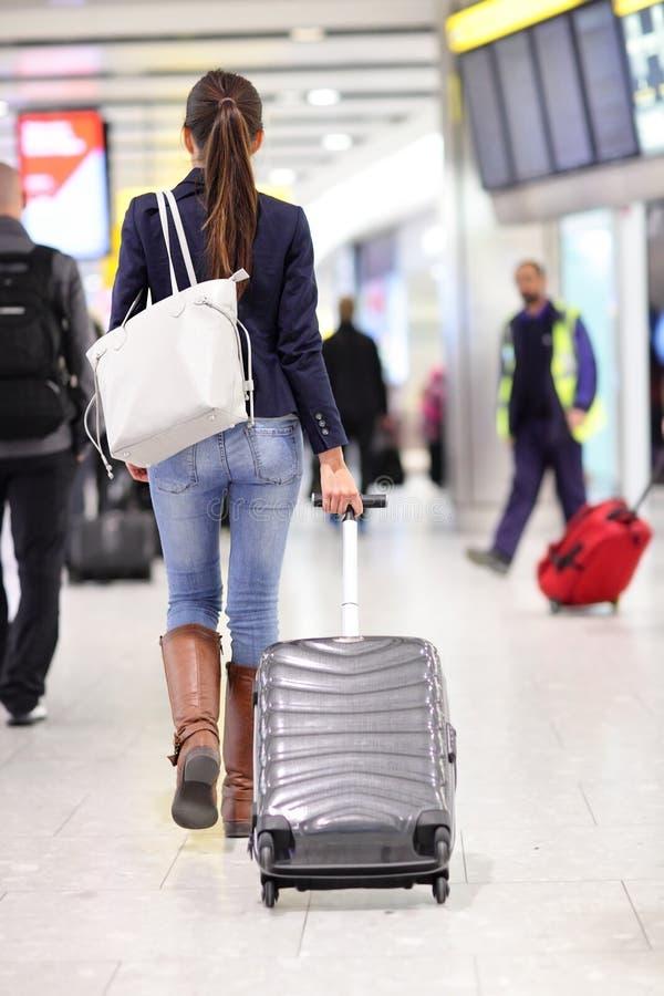 Resa kvinnan som går i en flygplats med bagage arkivfoto