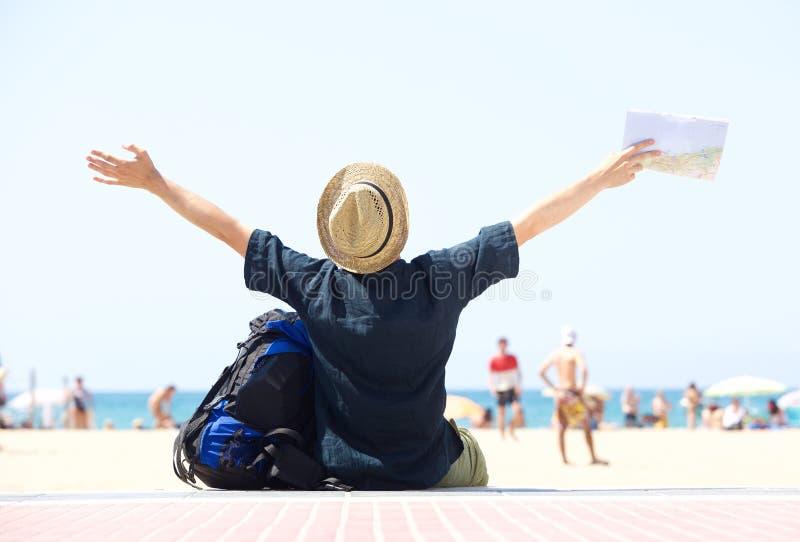 Resa mansammanträde vid stranden med utsträckta armar royaltyfria foton