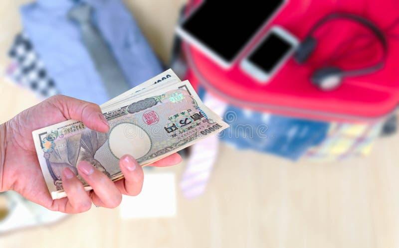Resa på kostnad, handkvinna med japanska valutayensedlar royaltyfri bild