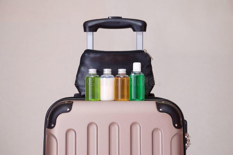Resa toalettartiklar, små plast- flaskor av hygienprodukter på resväskan arkivbilder