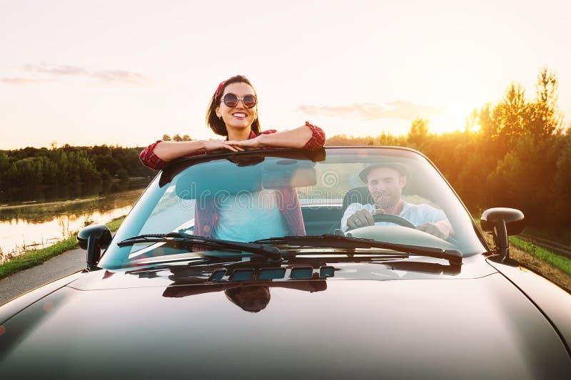 Resa vid förälskad dgo för bil- couplr med cabrioletbilen i solnedgång arkivbild