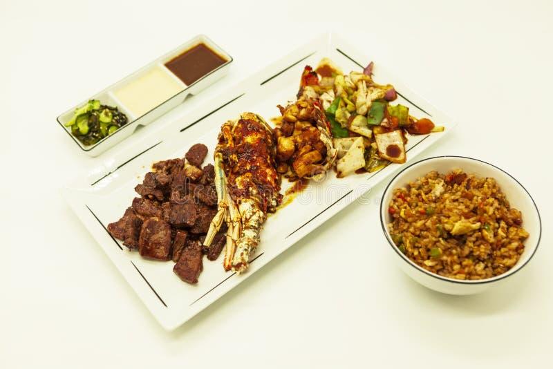 Resaca y césped, langosta frita y participación jugosa con un adorno de verduras fritas con con arroz y salsas calientes chinos f fotografía de archivo