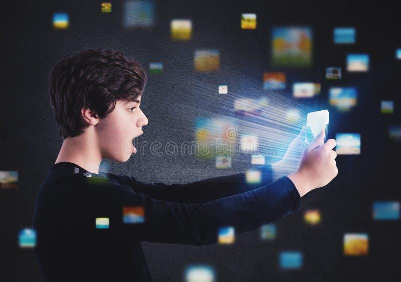 Resacas del muchacho en Internet con una tableta imagenes de archivo