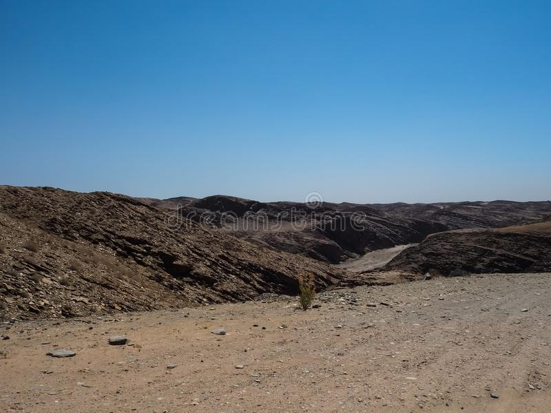 Resan till och med utmärkt vaggar bakgrund för bergtexturlandskapet av unik geografi för den Namib öknen med blixtrande stenjordn arkivbild