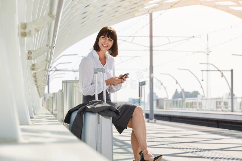 Resande affärskvinna med den smarta telefonen och bagage royaltyfria bilder