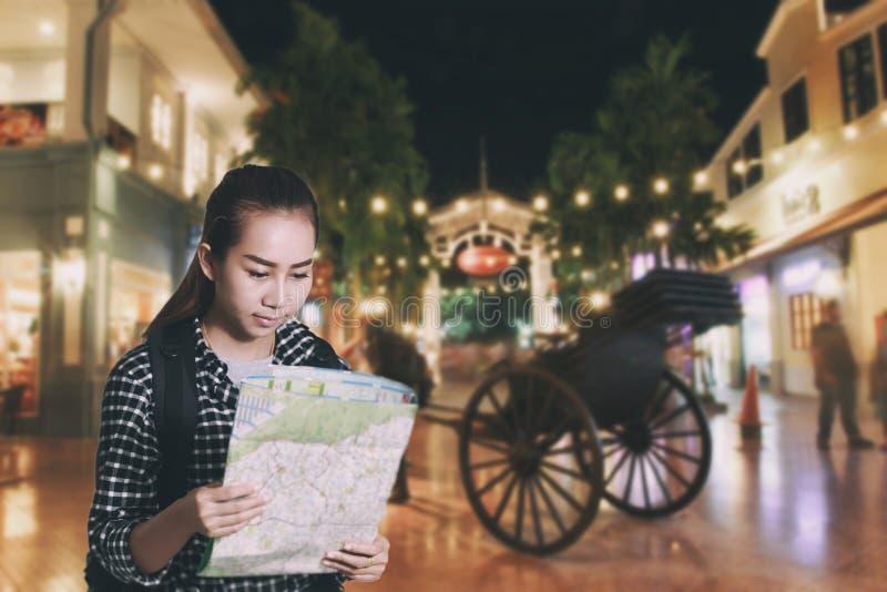 Resande asiatisk kvinna med ryggsäcken och seöversikt på staden på D royaltyfri bild