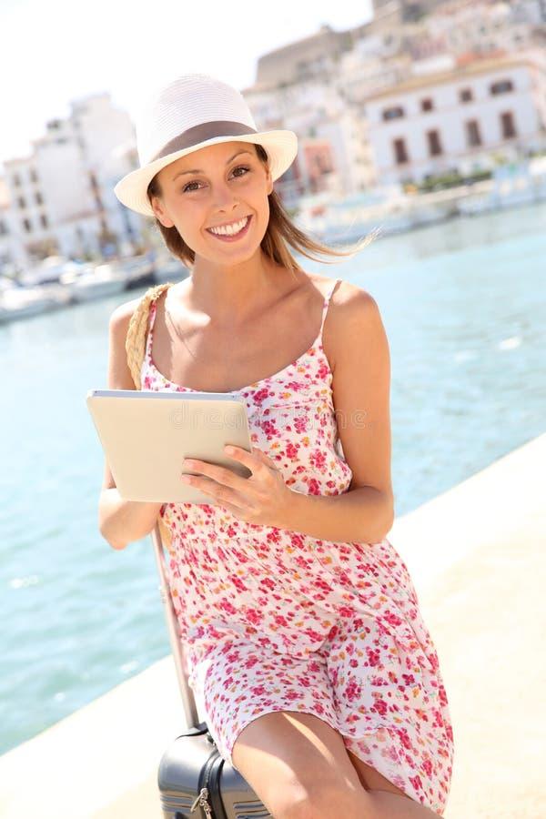 Resande för ung kvinna genom att använda minnestavlan på ferier royaltyfri foto