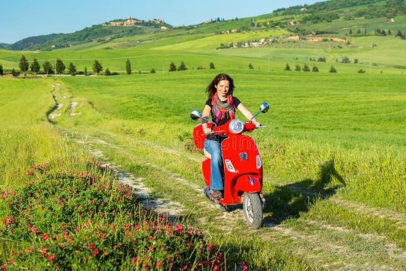 Resande för ung kvinna vid en sparkcykel royaltyfria bilder