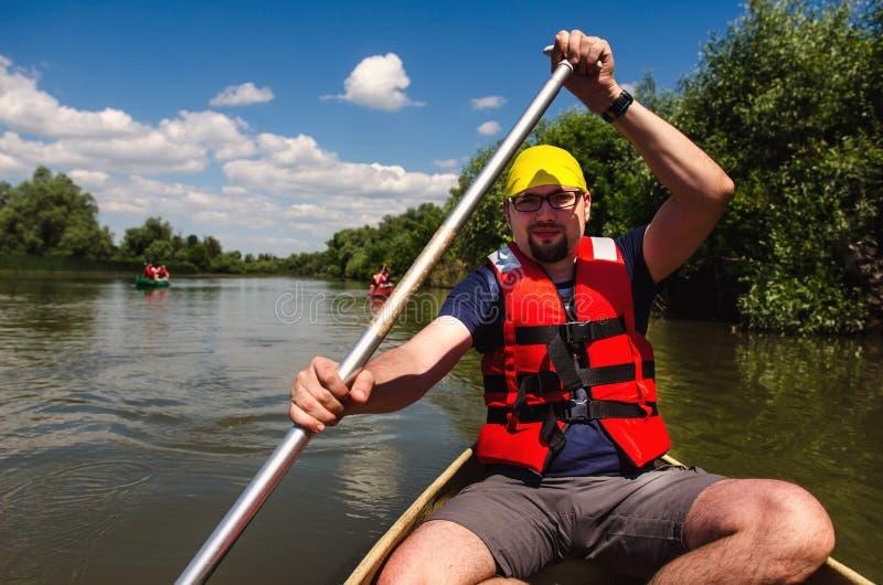 Resande för ung man i en kanot royaltyfri foto