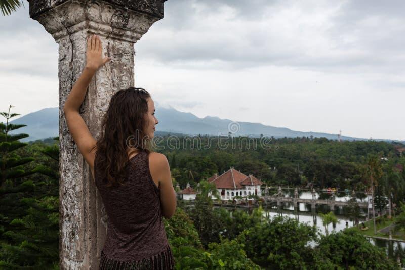 Resande flicka för serie i Asien härlig flicka med långt mörkt hår i den eleganta gråa klänningen som poserar på den gamla bron i arkivfoton