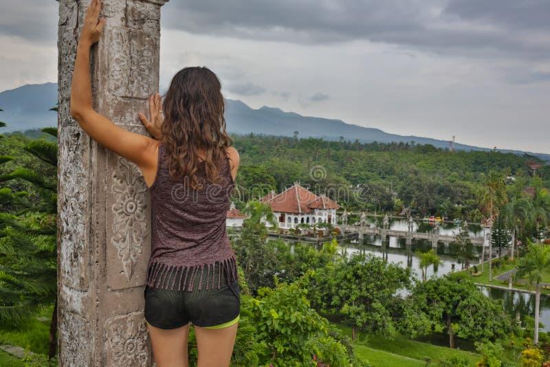 Resande flicka för serie i Asien härlig flicka med långt mörkt hår i den eleganta gråa klänningen som poserar på den gamla bron i fotografering för bildbyråer