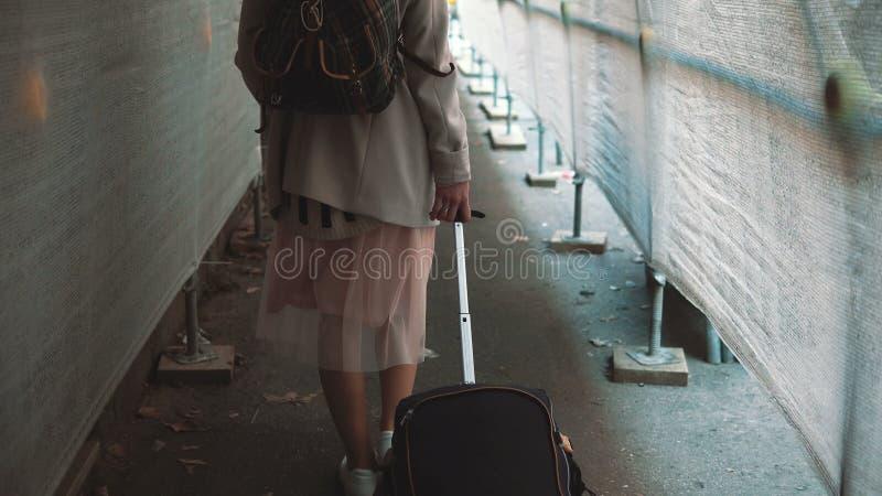 Resande flicka med ryggsäcken och resväskan som går till och med konstruktionskorridoren Ung kvinna som flyttar sig till den nya  royaltyfria foton