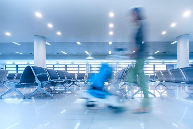 Resande kvinna i flygplatsterminal Abstrakt begrepp vinkar blur royaltyfri foto