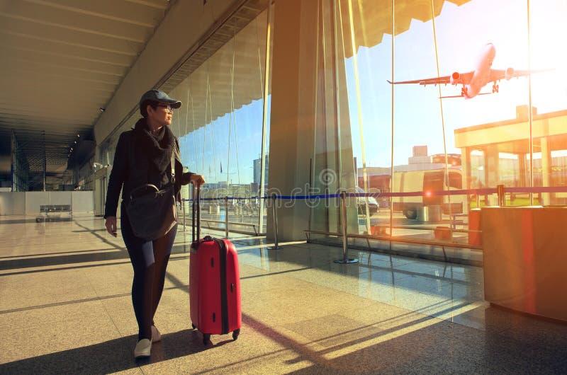 Resande kvinna och bagage som går i flygplatsterminal och luft royaltyfri bild