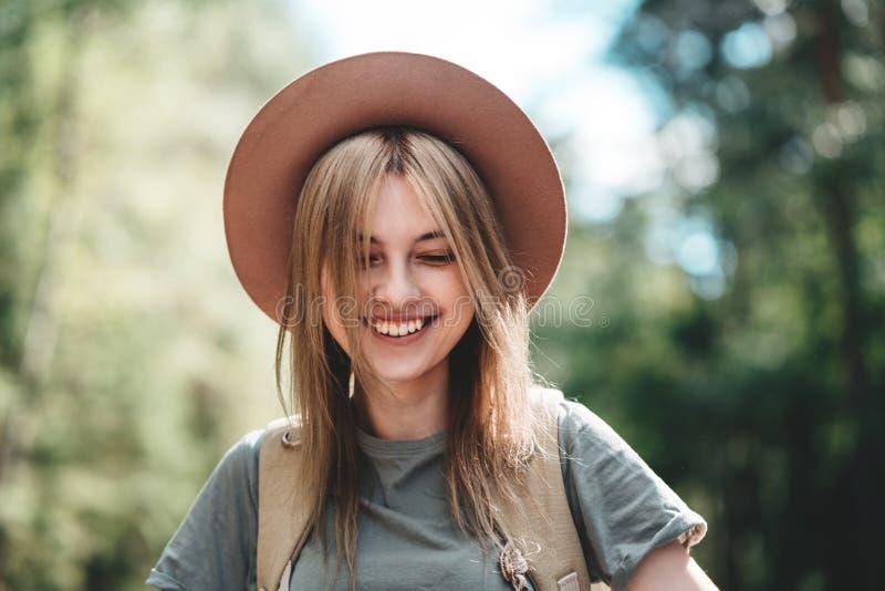 Resande och le för hatt för ung stilig kvinna bärande arkivbild