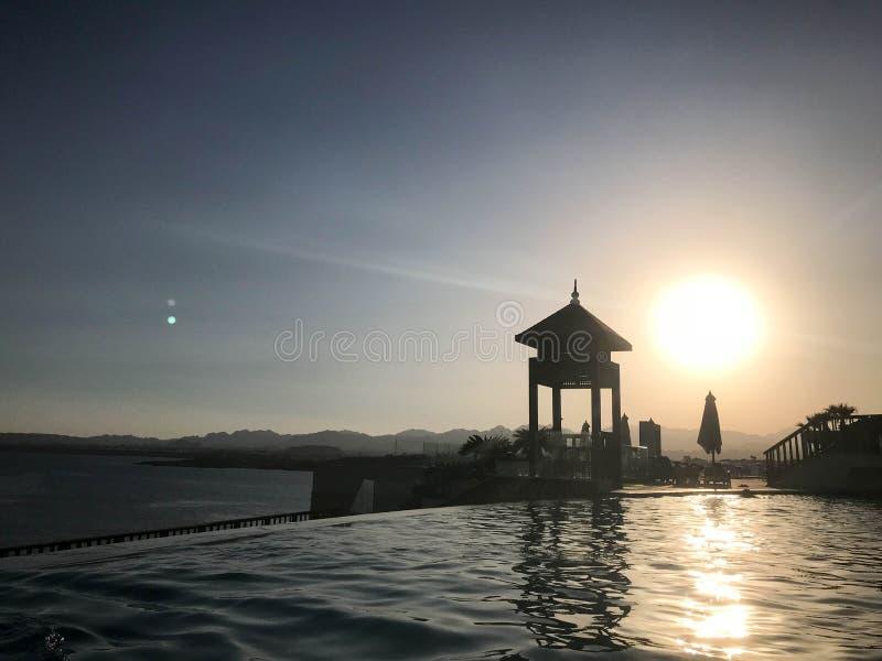 Rescate la cabina, elévese, rescate los posts al borde del agua de una piscina lujosa del infinito que se combina con el horizont imágenes de archivo libres de regalías