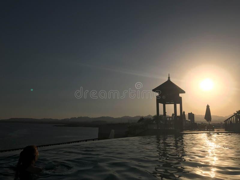 Rescate la cabina, elévese, rescate los posts al borde del agua de una piscina lujosa del infinito que se combina con el horizont fotografía de archivo