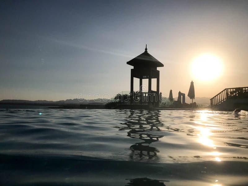 Rescate la cabina, elévese, rescate los posts al borde del agua de una piscina lujosa del infinito que se combina con el horizont fotografía de archivo libre de regalías